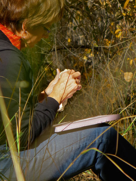 Resident hand modeling clay along the bosque.