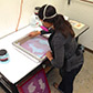 Oakland artist Michelle Murillo in the studio, printing with glass powder